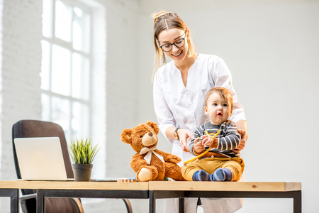 Young woman pediatrician taking care of a baby boy sitting on the table at the office