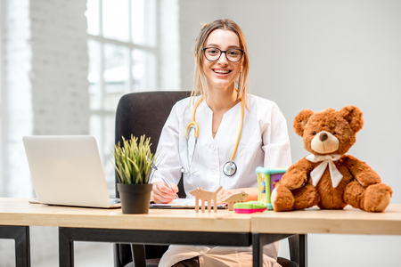Portrait of a young woman pediatrician in medical gown sitting at the office Reklamní fotografie