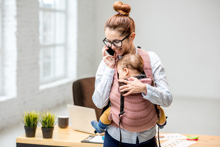 Young multitasking businesswoman standing with her baby son during the work at the office