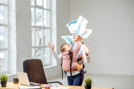 Multitasking and exhausted businesswoman throwing up a documents standing with her baby son during the work at the office Stock Photo