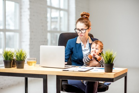 Young multitasking businessmam dressed in the suit working with laptop and documents sitting with her baby son at the office Standard-Bild