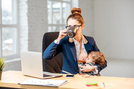 사무실에서 커피를 마시고 휴식을 취하는 동안 유방과 그녀의 아기가 아들을 먹는 젊은 멀티 태스킹 businessmam 스톡 콘텐츠