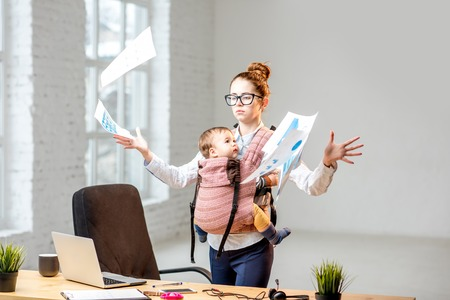 Multitasking and exhausted businesswoman throwing up a documents standing with her baby son during the work at the office 免版税图像