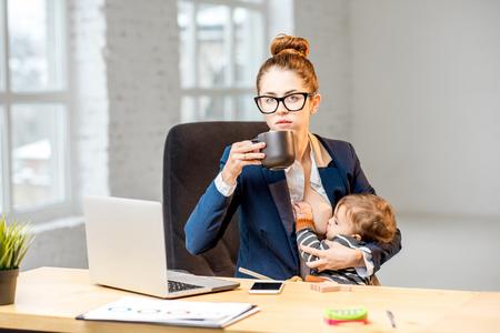 Joven multitarea businessmam alimentando a su bebé con pecho mientras toma un descanso tomando café en la oficina