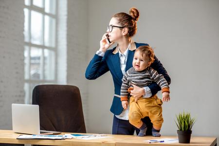 Jovem businessmen multitarefa vestida no terno falando em pé de telefone com seu filho bebê no escritório