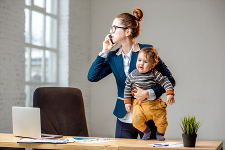 Young multitasking businessmam dressed in the suit talking phone standing with her baby son at the office
