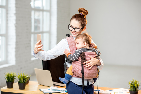 Businesswoman making selfie photo standing with her baby son at the office Фото со стока