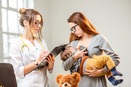 Moeder die haar babyjongen voedt tijdens het overleg met jonge vrouwenpediater die zich in het witte bureau bevinden