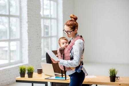 オフィスでの仕事中に赤ちゃんの息子と一緒に立っている若いマルチタスクビジネスウーマン