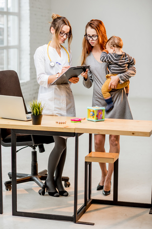 Mother with her baby boy during the consultation with young woman pediatrician standing in the white office Foto de archivo
