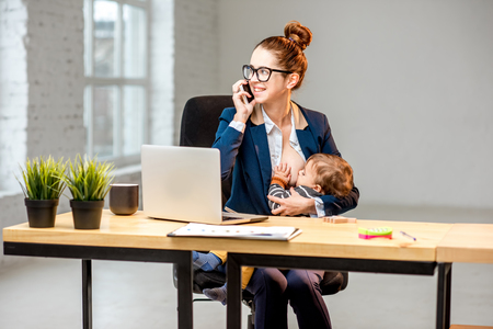 Young multitasking businessmam feeding her baby son with breast while working at the office