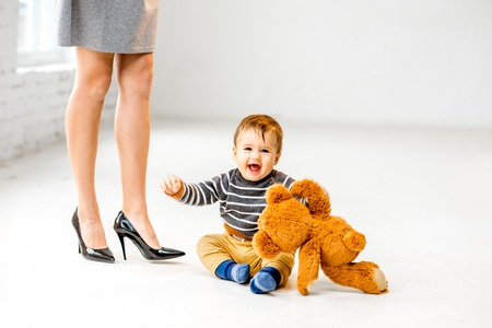 Baby boy playing near the womans beautiful legs on the white floor