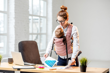 Exhausted businesswoman working with paper documents with her baby son at the office Foto de archivo