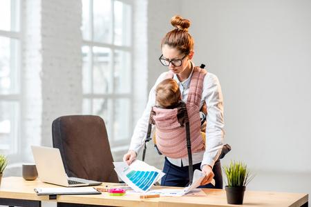 Uitgeputte zakenvrouw werken met papieren documenten met haar baby zoon op kantoor