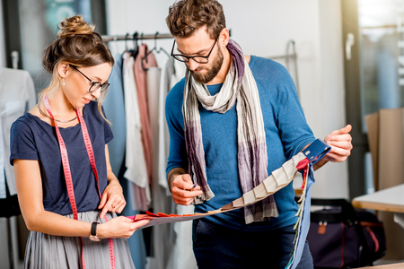 Couple of fashion designers choosing fabric standing at the studio full of tailoring tools and equipment