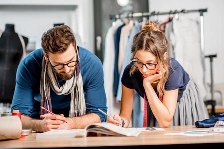 Pareja de diseñadores de moda trabajando con bocetos de ropa en el estudio lleno de herramientas y ropa de sastrería Foto de archivo - 92356865