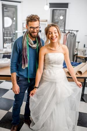 Jonge vrouw die huwelijkskleding passen met man kleermaker die zich bij de naaiende studio bevinden