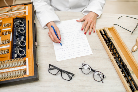 Senior ophthalmologist writing scientific work on the table with eyeglasses and different lenses Stock Photo
