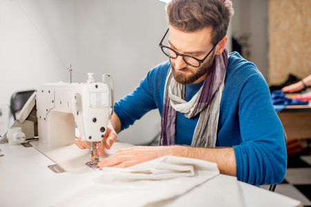 Nähendes Gewebe des hübschen Schneiders mit einer Nähmaschine am Studio