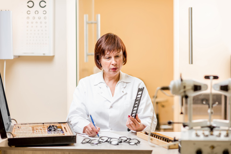 Portrait of a senior woman ophthalmologist in unifrom sitting with different optical devices and eyeglasses during the work in the office Stock Photo