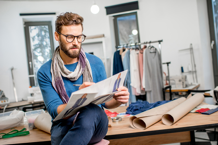 Portrait of a handsome fashion designer sitting with clothing sketches at the studio full of tailoring tools and clothes