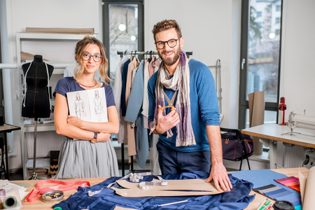 Portrait of a couple of fashion designers working with fabric and clothing sketches at the studio full of tailoring tools and equipment