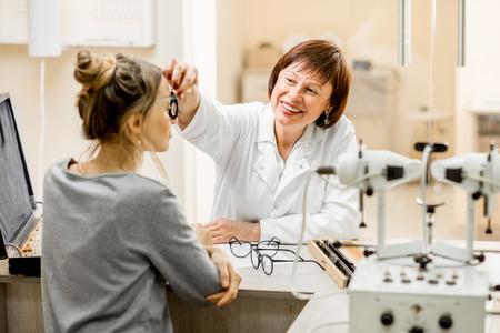 Älterer Frauenaugenarzt mit jungem weiblichem Patienten während der Beratung im ophthalmologischen Büro
