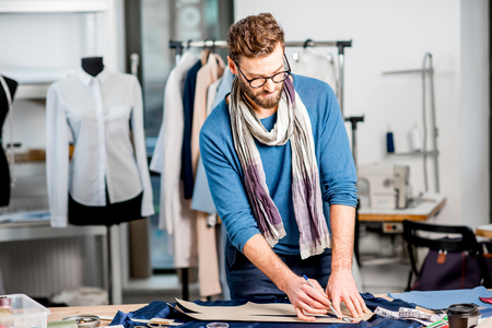 Handsome fashion designer working with fabric at the studio full of tailoring tools Stock Photo