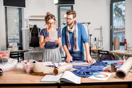 Couple of fashion designers working with fabric and clothing sketches at the studio full of tailoring tools and equipment Stock Photo