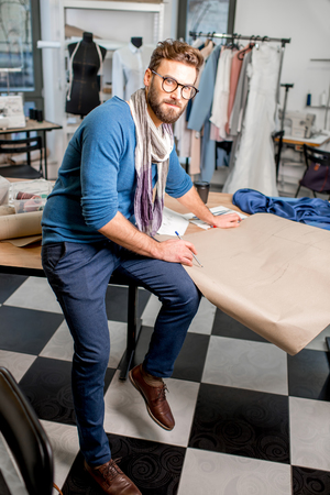 Portrait of a handsome fashion designer sitting with paper sketches at the studio full of tailoring tools and clothes