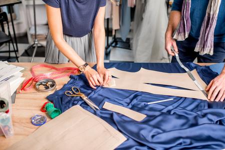 Blaues Gewebe von Schneidereiwerkzeugen auf dem Tisch voll schneiden. Großaufnahme über die Hände und den Stoff ohne Gesicht Standard-Bild