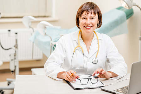 Portrait of a smiling seinor doctor sitting with laptop and documents in the gynecological office Stock Photo