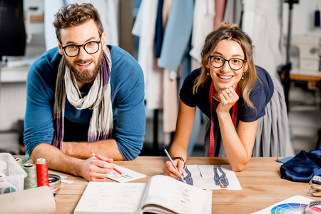 Couple of fashion designers working with clothing sketches at the studio full of tailoring tools and clothes Stock fotó - 92357527