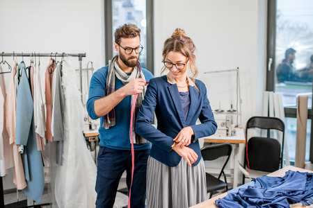 Handsome tailor measuring jacket on the woman client standing at the studio full of tailoring tools and equipment