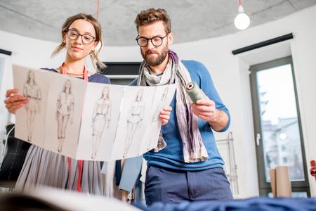 Couple de créateurs de mode travaillant avec des croquis de vêtements au studio Banque d'images - 92357541