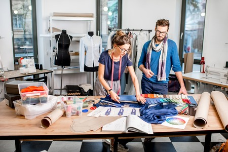 Couple of fashion designers working with fabric and clothing sketches at the studio full of tailoring tools and equipment Фото со стока