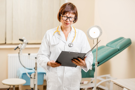 Portrait of a senior woman gynecologist standing in the office with gynecological chair and lamp on the background