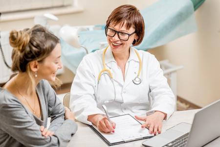 職場での相談中にシニア婦人科医を持つ若い女性患者
