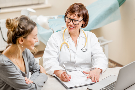 Jonge vrouwenpatiënt met een hogere gynaecoloog tijdens het overleg in het bureau