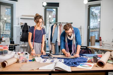 재단 도구 및 장비의 전체 스튜디오에서 직물로 일하고 패션 디자이너의 커플