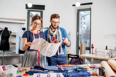 Couple of fashion designers working with clothing sketches at the studio Stock Photo