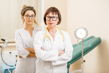 Portrait of a senior doctor with young assistant standing in the gynecological office