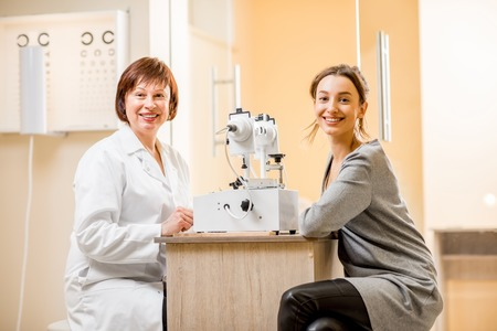 Portrait of senior woman ophthalmologist with the young female patient sitting in the ophthalmological office