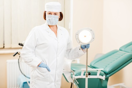 Portrait of a senior woman gynecologist in medical gown and hat preparing for procedure in the gynecological office