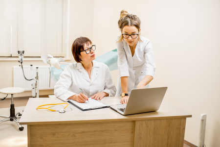 Senior doctor and young woman assistant working together with laptop and documents in the gynecological office Stock Photo - 92409447