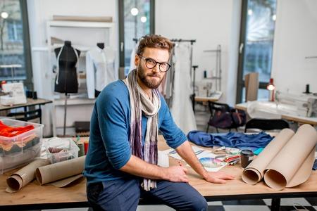 Portret van een knappe modeontwerper zitten met papieren schetsen in de studio vol met afstemming gereedschappen en kleding