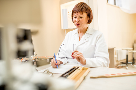 Portrait of a senior woman ophthalmologist in unifrom writing scientific work sitting in the office