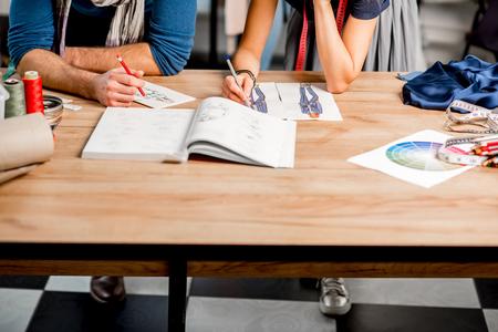 패션 디자이너 드로잉 의류 스케치 테이블에 그리기 커플. 얼굴이없는 테이블에 근접 촬영보기