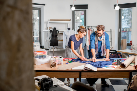 Couple of fashion designers working with fabric at the studio full of tailoring tools and equipment