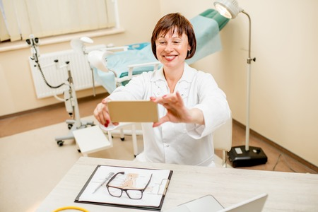 Smiling seinor doctor making selfie photo sitting in the gynecological office